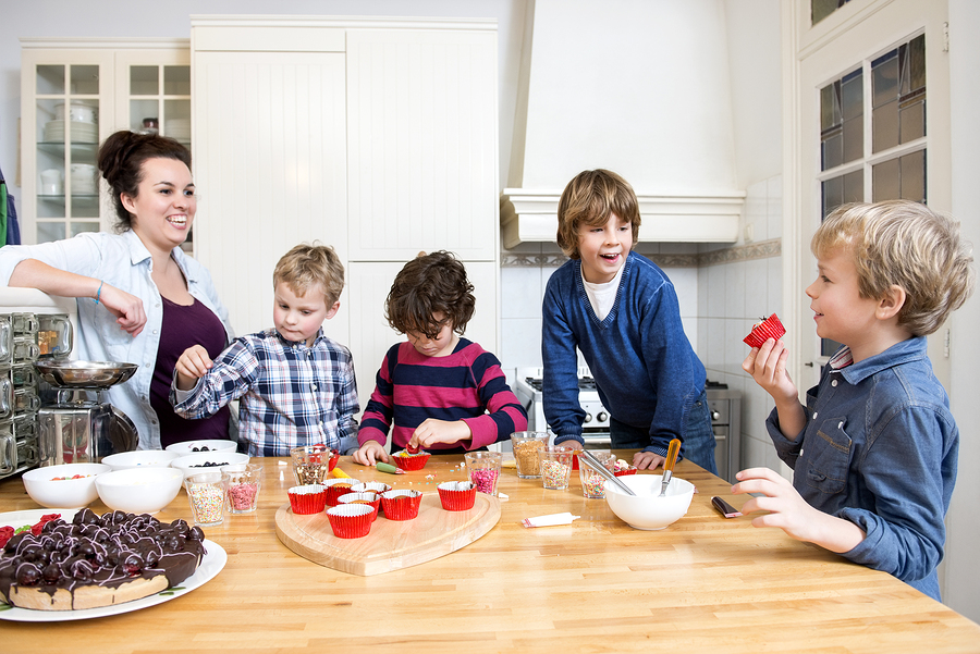 Boys and girls decorating cupcakes at a kitchen counter during a baking workshop for kids at a birthday party