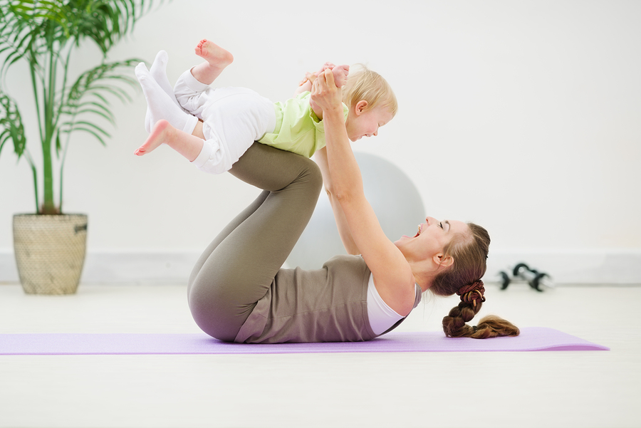 Healthy mother and baby making gymnastics at room